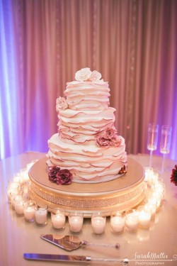 Three tiered fondant ruffle cake with plum ombre dusted edges and sugar flowers