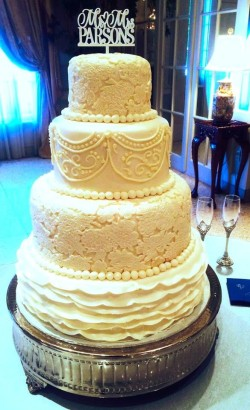 Four tiered fondant cake with ruffles, lace overlays and hand piping