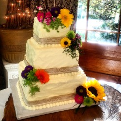Three tiered square textured buttercream cake with fresh flowers and burlap lace