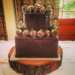 Two tiered chocolate ganache dripped groom's cake with chocolate covered strawberries