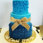 Three tiered blue ombre buttercream cake with rosettes and burlap ribbon