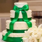 Four tiered smooth buttercream cake with piped dots and satin ribbon