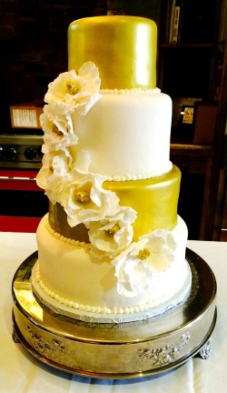 Four tiered fondant white and gold cake wtih sugar magnolias