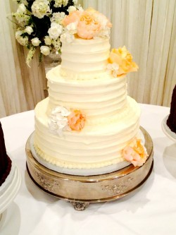 Three tiered horizontal lined buttercream cake with fresh flowers