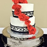 Two tiered smooth buttercream cake with hand piped scrollwork and red cascading sugar roses