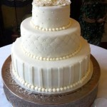 Three tiered fondant cake with pearls, quilting, stripes and fondant ruffled flowers