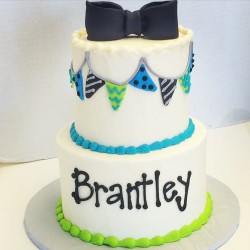 Two tiered smooth buttercream cake with fondant details