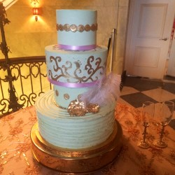 Four tiered mint cake with gold embellishments, lavender ribbon and feather