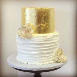Two tiered buttercream cake with horiztonal lined texture, gold leaf and gold tipped ruffle flowers