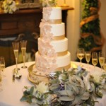 Four tiered smooth buttercream cake with satin ribbon and fondant cascading lace flower overlays