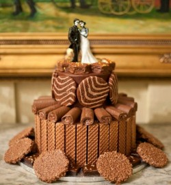 Two tiered chocolate groom's cake with snack cake decorations