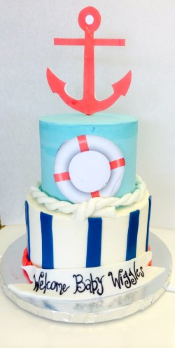 Two tiered buttercream baby shower cake with fondnat decor