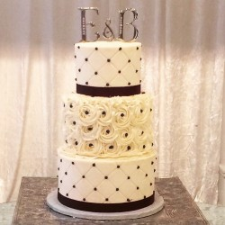 Three tiered cake buttercream cake with quilting and rosettes, satin ribbon and piped dots