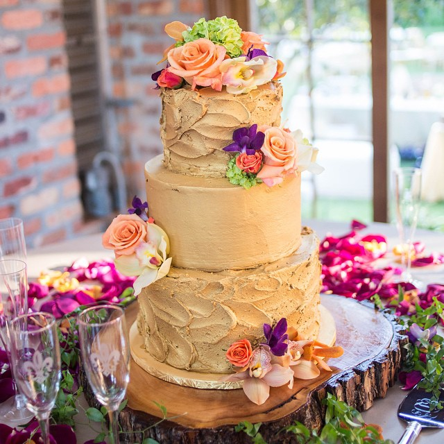 Three tiered smooth and textured gold buttercream cake with fresh flowers