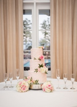 Three tiered pink plastered buttercream with fresh flowers