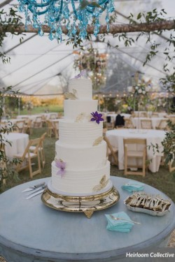 Five tiered smooth and lined buttercream wedding cake with fondant gold leaves and fresh flowers