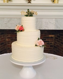 Three tiered lined textured buttercream cake adorned with fresh flowers