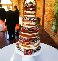 Four tiered naked wedding cake adorned with fresh fruit