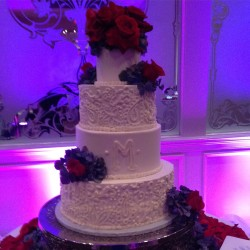 Four tiered smooth and paisley piped buttercream cake with fresh flowers