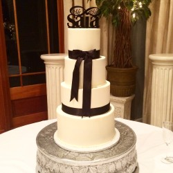 Four tiered smooth buttercream cake with black satin ribbon