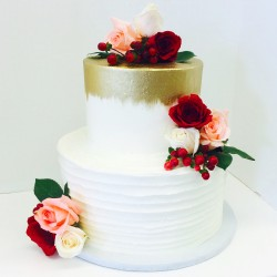 Two tiered smooth and lined textured buttercream cake with gold accents and fresh flowers for a bridal shower