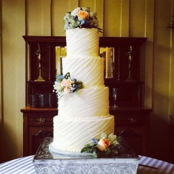Four tiered swooped line textured buttercream cake with fresh flowers
