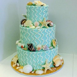Three tiered blue buttercream cake with sea shells