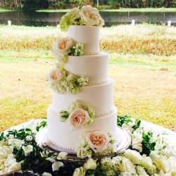 Four tiered smooth buttercream cake adorned with fresh flowers