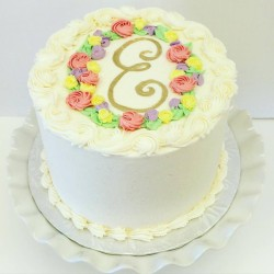 Sweet buttercream cake with piped flowers and baby's initial