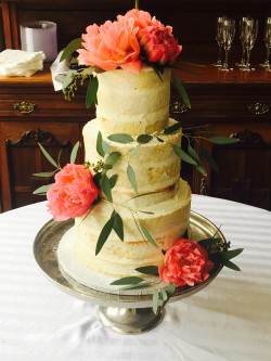 Three tiered naked cake with fresh flowers and a powdered sugar sprinkle