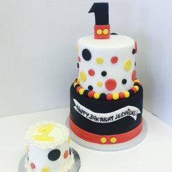 Two tiered Mickey Mouse inspired fondant birthday cake with matching smash cake
