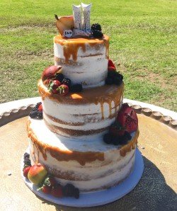 Three tiered semi-naked cake garnished with fresh fruit and caramel drizzle