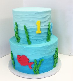 Two tiered ombre waved buttercream cake with fondant decor