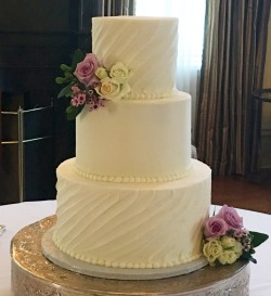 Three tiered buttercream wedding cake with diagonal swooped desing