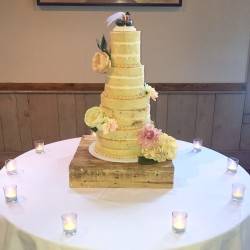 Three tiered naked cake adorned with fresh flowers