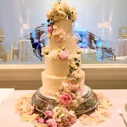 Four tiered semi plastered cake with fresh flowers