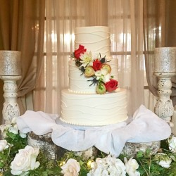 Three tiered smooth buttercream cake with piped design and fresh flowers