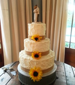 Three tiered plasterd buttercream cake with burlap ribbon and fresh sunflowers