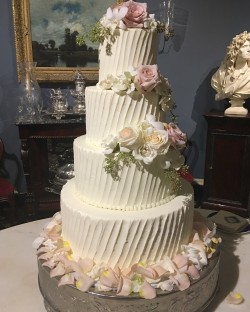 Four tierd diagonal lined buttercream cake with fresh flowers