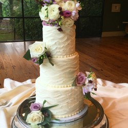 Three tiered wavy horizontal lined buttercream cake with fresh flowers